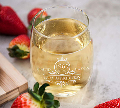 "Imprinted ergonomic wine glass with text ""VINTAGE 1969 AGED TO PERFECTION"". Excellent gift for 50 year old birthday party."