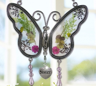 Made of glass and metal a butterfly suncatcher with silver heart charm with Sister engraved on it. Real flowers pressed between glass.